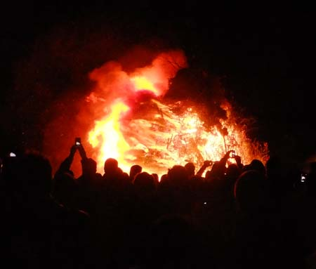 Bonfire burning with crowd of people