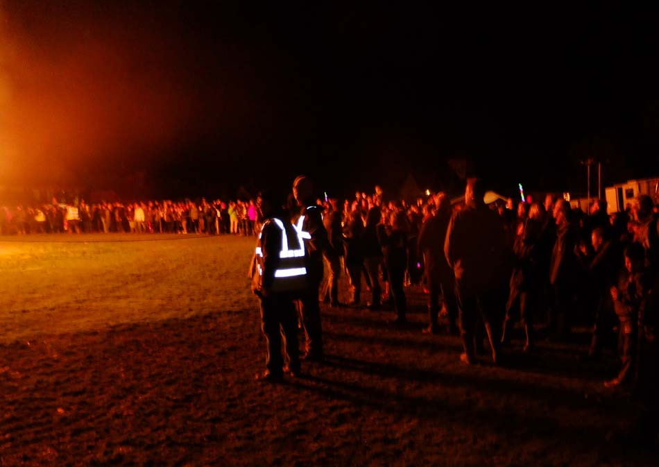 Onlookers at bonfire at night